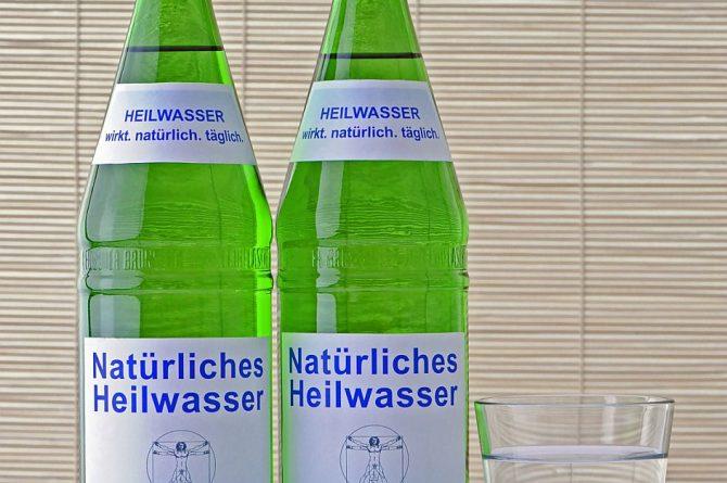 Zwei Heilwasserflaschen und Glas vor Bambusrollo