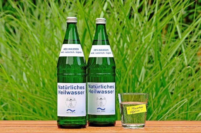 Heilwasserflaschen und Glas vor Gräsern