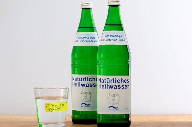 Heilwasserflaschen und Glas mit Notiz zwei Flaschen täglich