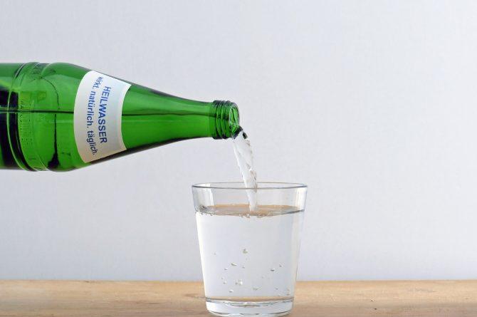 Heilwasser einschenken aus Flasche von links