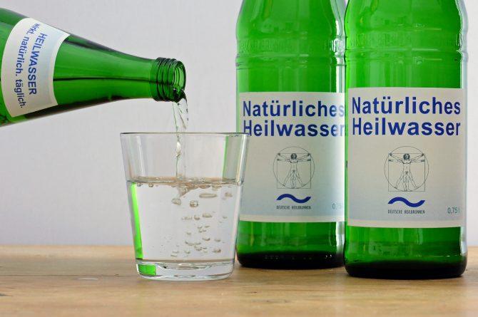 Heilwasser einschenken und zwei Flaschen