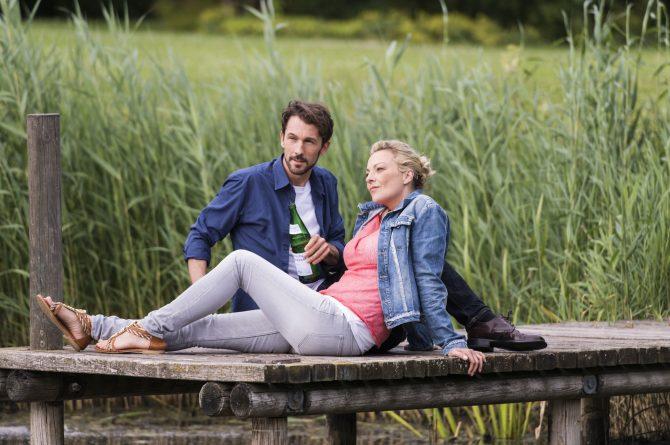 Paar sitzt am Steg_mit Heilwasserflasche