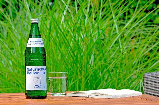 Heilwasserflasche und Glas an Tisch im Grünen