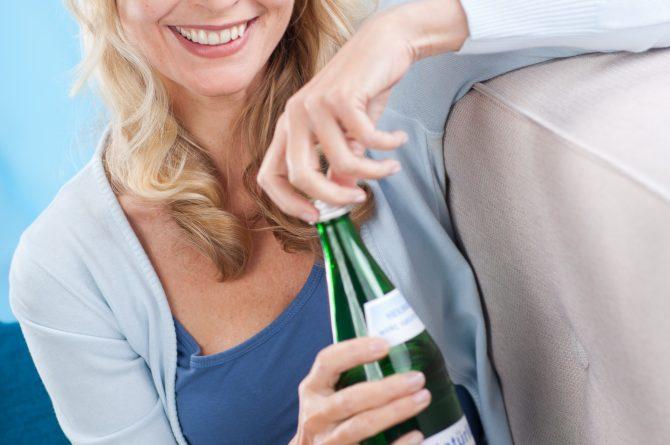 Frau middle-age mit Heilwasserflasche auf Sofa_808