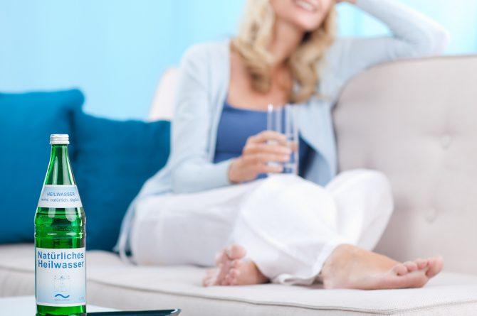 Heilwasserflasche mit Frau auf Sofa im Hintergrund_650