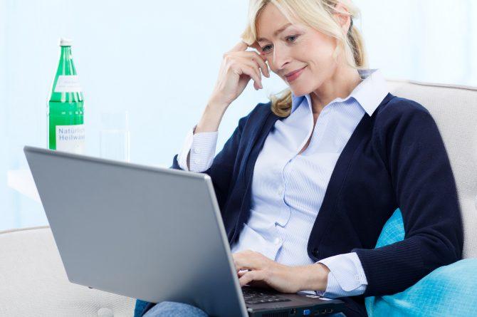 Frau middle-age mit Laptop_Heilwasserflasche im Hintergrund_861
