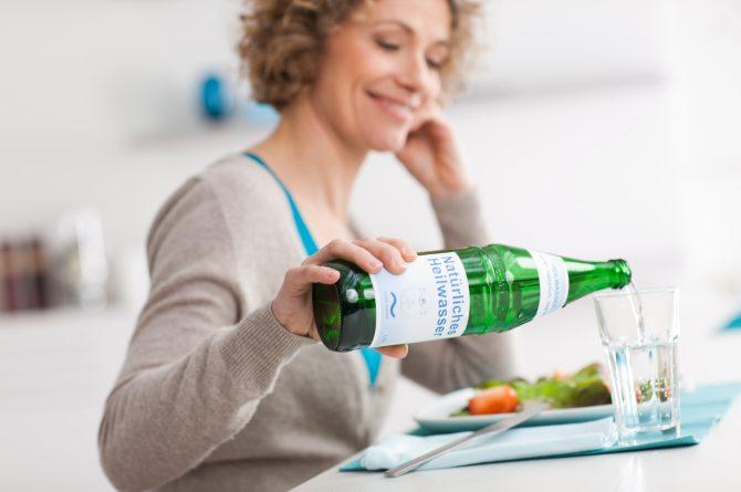 Essen_Frau schenkt sich Heilwasser ein_1399