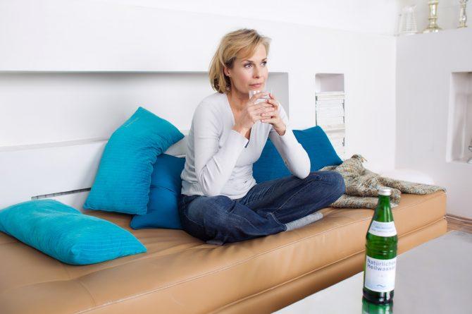 Frau mit Wasserglas auf Sofa_1463