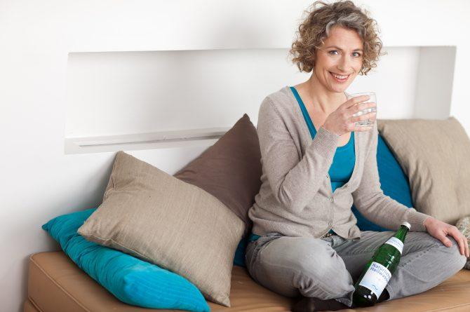Frau middle-age mit Wasserglas und Heilwasserflasche_1525