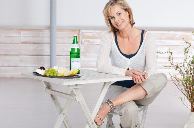 Frau an Gartentisch mit Heilwasserflasche_1617