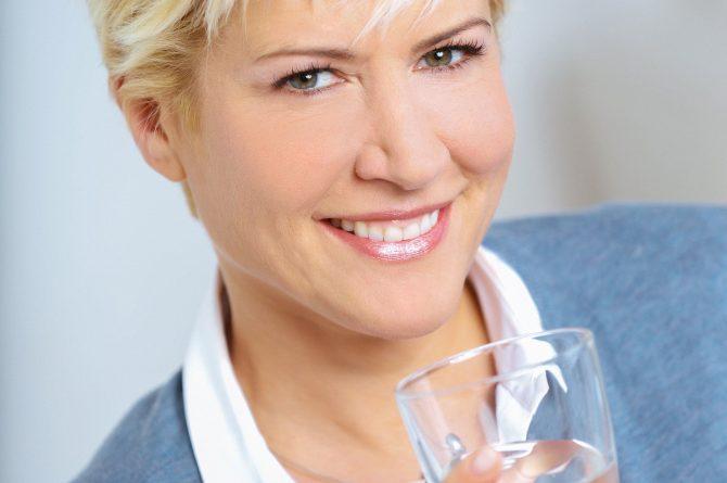 Junge Frau in hellblauer Jacke mit Heilwasserglas_3055