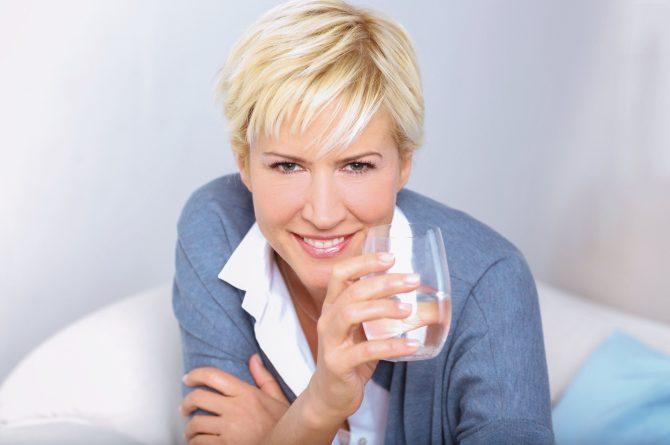 Junge Frau mit Wasserglas Arme überkreuzt_3298