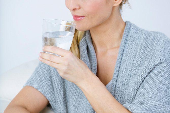 Frau middle-age in beiger Stola mit Wasserglas_3668