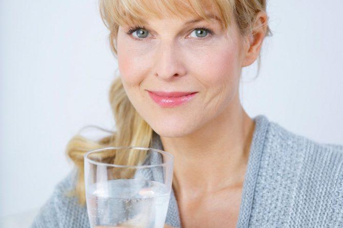 Frau middle-age in beiger Stola mit Wasserglas_3677