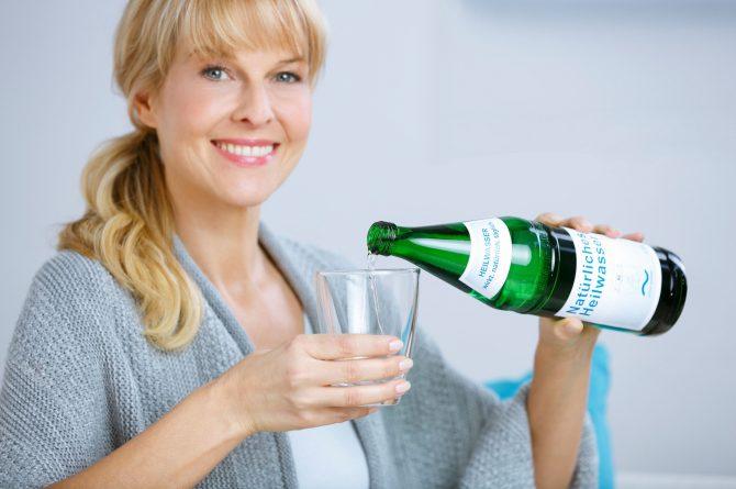 Frau middle-age schenkt Heilwasser ins Glas_3701