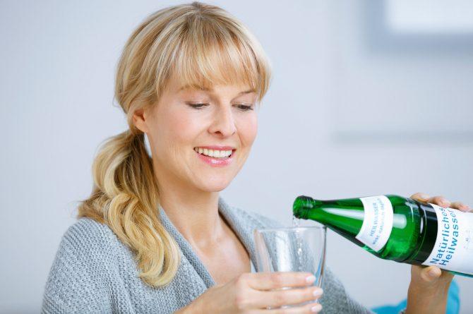 Frau schenkt Heilwasser ins Glas_3703