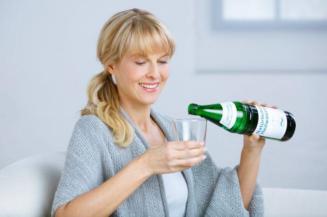 Frau gießt Heilwasser ins Glas_3714
