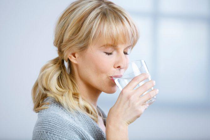 Frau mit geschlossenen Augen trinkt Heilwasser_3881