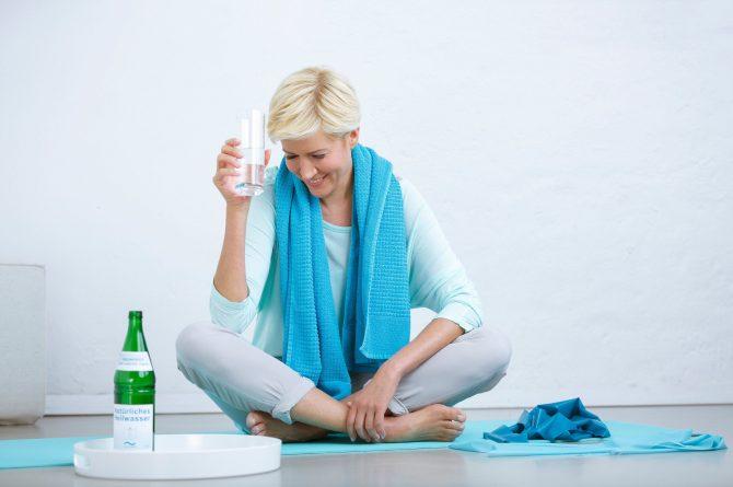 Junge Frau auf Gymnastikmatte trinkt Heilwasser_3934