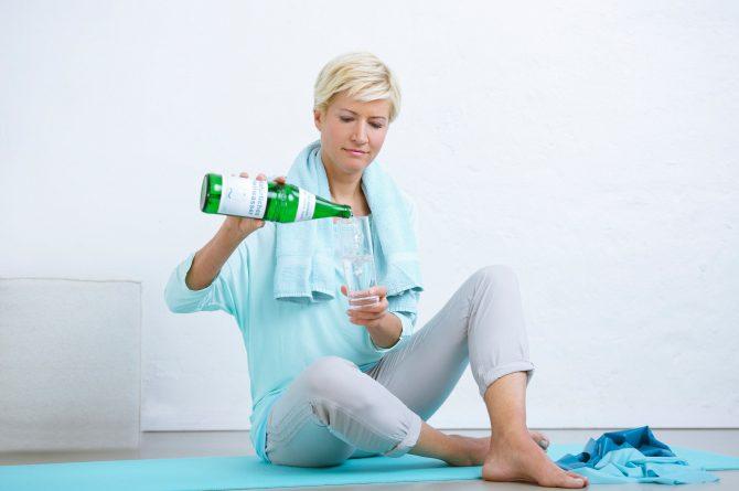 Junge Frau auf Gymnastikmatte schenkt sich Heilwasser ein_3978