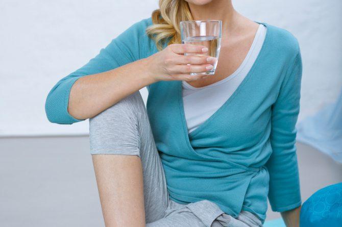 Trinken und Sport_Frau auf Yogamatte mit Heilwasserglas_4434