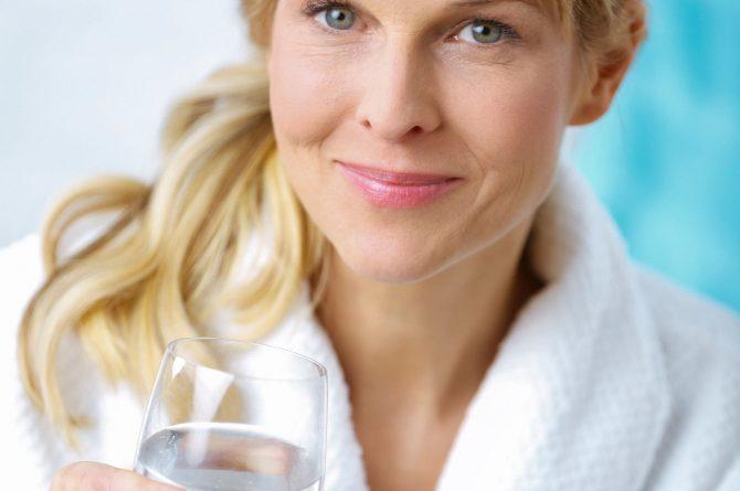 Wellness_Frau im Bademantel mit Heilwasserglas_4922