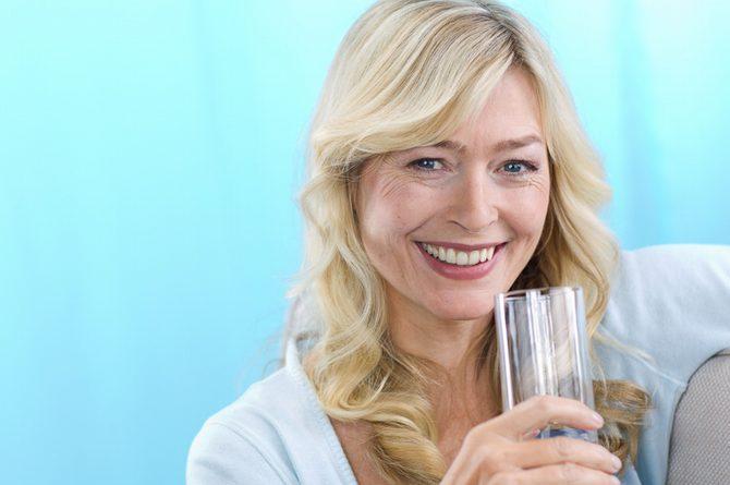 Frau middle-age mit Wasserglas vor blauem Hintergrund_765