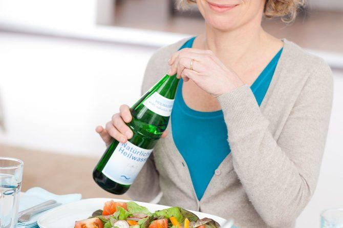 Frau mit Heilwasserflasche beim Salatessen