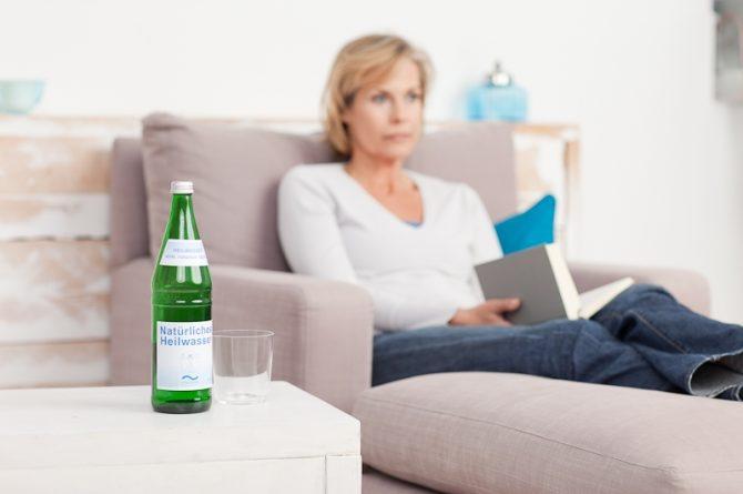 Heilwasserflasche_Frau im Hintergrund